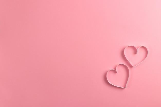 Kompozycja na walentynki luty. delikatne różowe tło i różowe serca wycięte z papieru.