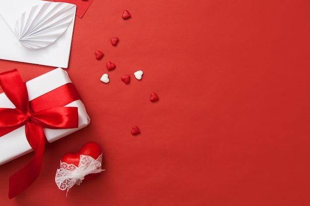 Kompozycja na walentynki. prezent, koperta, serce i serca. czerwone i białe połączenie z