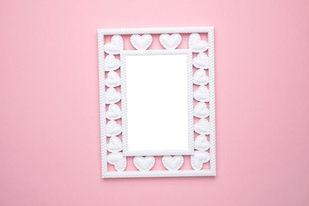 Kompozycja na walentynki. ramka na zdjęcia z sercami na pastelowym różowym tle. ślub. urodziny. szczęśliwego dnia kobiety. dzień matki. leżał na płasko, widok z góry, miejsce na kopię
