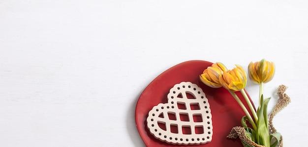 Kompozycja na walentynki z widokiem z góry na talerz, kwiaty i element dekoracyjny.