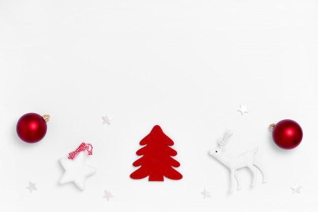 Kompozycja noworoczna i świąteczna. rama z czerwonych kulek, białych gwiazd, choinki na białym papierze. widok z góry, leżał płasko, lato.