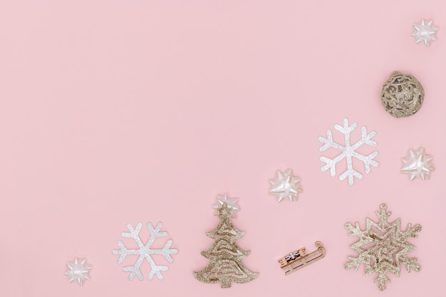 Kompozycja noworoczna i świąteczna. ramka ze złotej bombki, płatka śniegu, choinki, kokardek prezentowych, sań na pastelowym różowym papierze. widok z góry, płaski układ