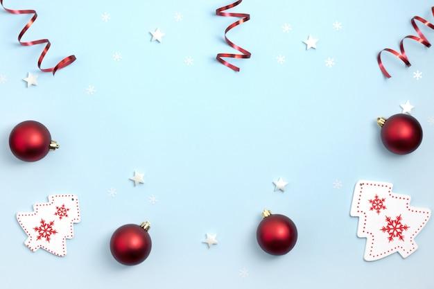 Kompozycja noworoczna i świąteczna. ramki frome czerwone i białe świąteczne zabawki na niebieskim tle papieru. widok z góry, leżał płasko, miejsce