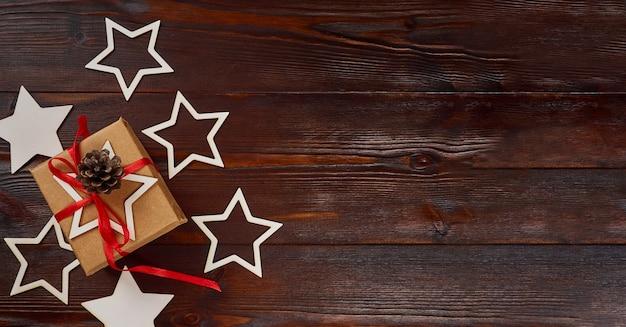 Kompozycja noworoczna. pudełko z czerwoną wstążką, ozdobne gwiazdki na ciemnym tle drewnianych. leżał płasko, widok z góry, miejsce na kopię, baner.