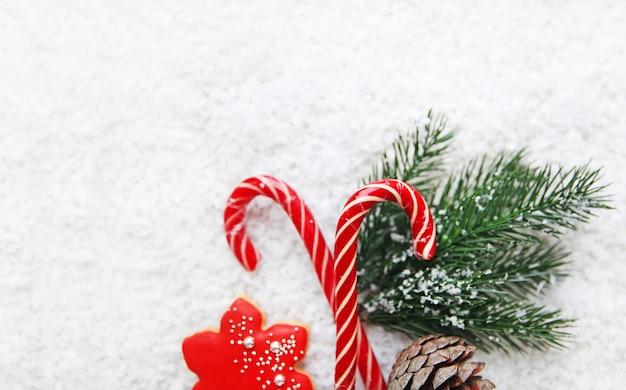 Kompozycja noworoczna świąteczne cukierki piernikowe gałęzie sosny na śnieżnym tle widok z góry