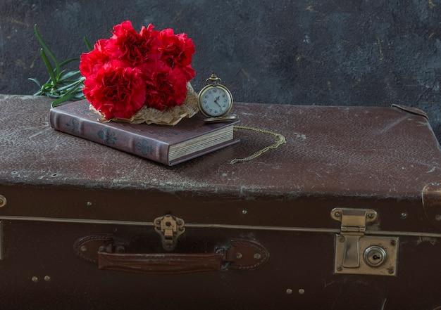 Kompozycja o wspomnieniach: czas wojny, walizka na pniu, zegary, goździki i książka