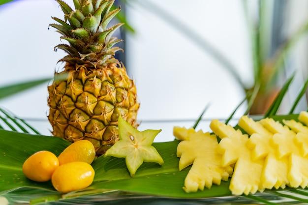 Kompozycja owoców egzotycznych, niektóre pokrojone w postaci ptaków, inne są całe, takie jak pomarańcze i ananas.