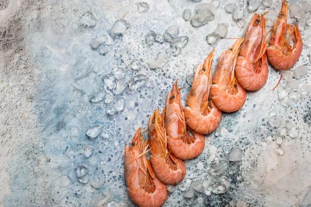 Kompozycja owoców morza płaska warstwa surowych krewetek z lodem na niebieskiej przestrzeni kopii