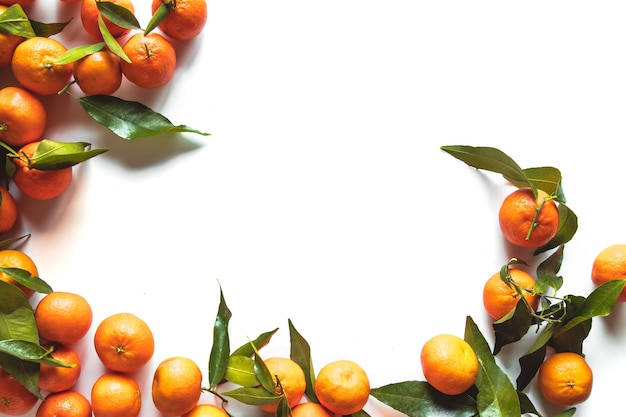 Kompozycja owoców pomarańczy z zielonymi liśćmi i plasterek na białym tle drewnianych, widok z góry