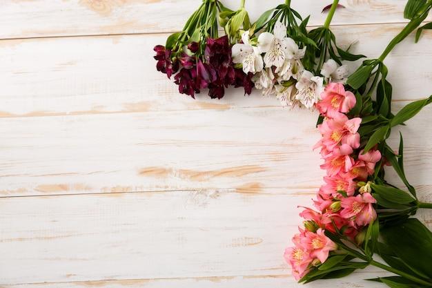 Kompozycja pięknych kwiatów na drewnie