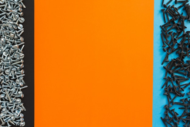 Kompozycja płasko świecąca z różnymi śrubami na czarnym, pomarańczowym i niebieskim tle. widok z góry koncepcji listy kontrolnej