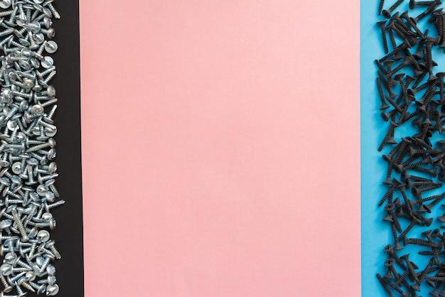 Kompozycja płasko świecąca z różnymi śrubami na czarnym, różowym i niebieskim tle. widok z góry koncepcji listy kontrolnej