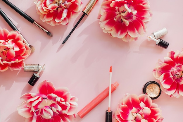Kompozycja płasko świecka z produktami do makijażu dekoracyjnego na różowym tle