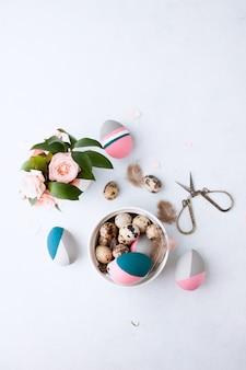 Kompozycja płasko ułożona z naturalnie barwionego jajka przepiórczego i kolorowych pisanek leżących w tacce na białej ściance z piór i róż. miejsce na tekst