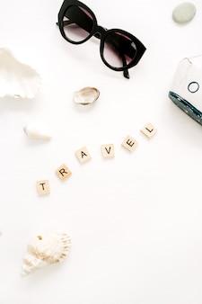 Kompozycja podróżna z okularami przeciwsłonecznymi, zabawkową łódką, muszelkami na białej powierzchni