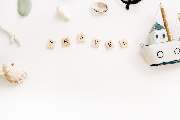 Kompozycja podróżna z zabawkową łódką, muszle na białej powierzchni