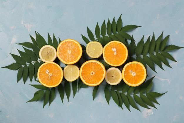 Kompozycja połówek cytryn i pomarańczy z zielonymi liśćmi na jasnoniebieskiej powierzchni, leżała płasko