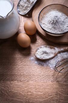 Kompozycja przedmiotów jaja łyżka corolla i mąka dzban mleka
