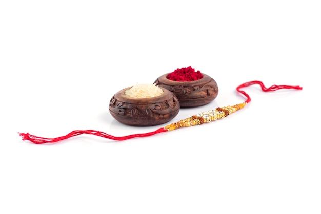 Kompozycja raksha bandhan z eleganckimi rakhi, rice grains i kumkum. tradycyjna indyjska opaska na nadgarstek będąca symbolem miłości między braćmi i siostrami.