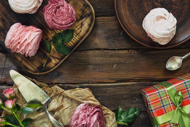Kompozycja różnych jagód, wiśni, bezy i kwiatów na ciemnej drewnianej powierzchni