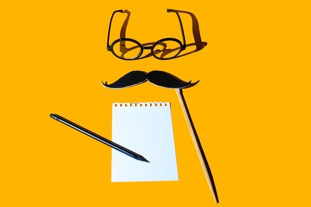 Kompozycja różnych przedmiotów. okulary, ołówek, wąsy, pusty arkusz notatnika. ciężkie cienie na żółtym tle