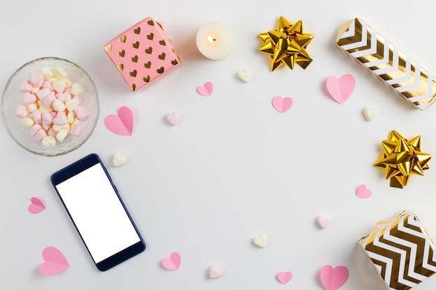 Kompozycja różowych serc wykonanych z papieru, prezentów, telefonu i pianek w kształcie serca