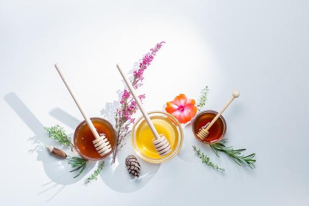 Kompozycja słoików z miodowymi pałeczkami i kwiatami