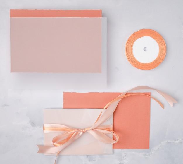 Kompozycja ślubna leżąca płasko z minimalistyczną makietą zaproszeń