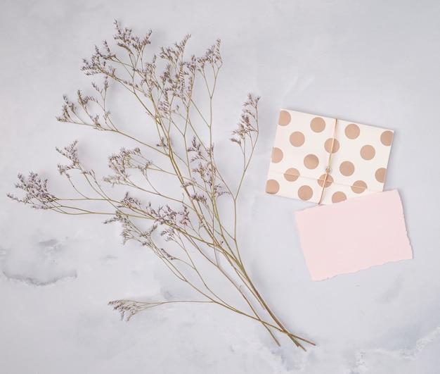 Kompozycja ślubna leżąca płasko z minimalistycznymi zaproszeniami