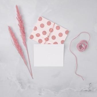 Kompozycja ślubna w widoku z góry z minimalistycznymi zaproszeniami