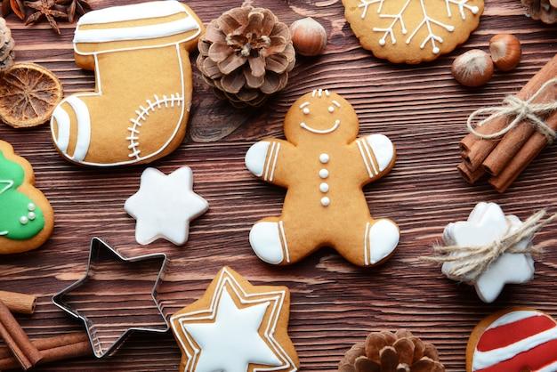 Kompozycja smacznych ciasteczek i świątecznych dekoracji na drewnianym stole, widok z bliska