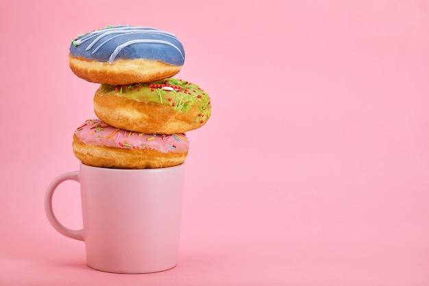 Kompozycja śniadaniowa kolorowych pączków z różnymi kolorami pączków i świeżej kawy na różowym tle