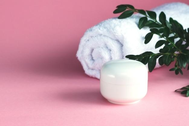 Kompozycja spa z białym ręcznikiem i butelką kremu na różowym tle