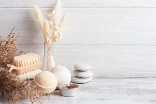 Kompozycja spa z kulami do kąpieli i suchymi kwiatami na rustykalnym tle w stylu monochromatycznym. ręcznik ze świecami i białymi kamykami. masaż gorącymi kamieniami dla jednej osoby. zabiegi kosmetyczne i relaksacyjne