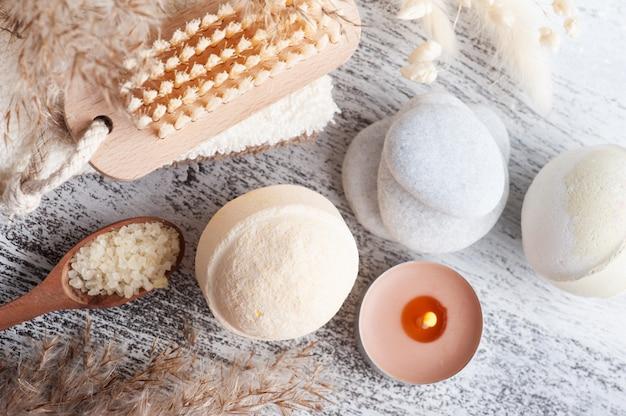 Kompozycja spa z kulami do kąpieli i suchymi kwiatami na rustykalnym tle w stylu monochromatycznym. ręcznik ze świecami i białymi kamykami.