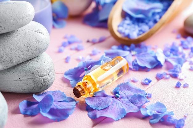 Kompozycja spa z kwiatami hortensji i butelką oleju na stole kolorów