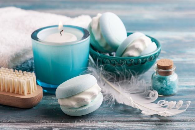 Kompozycja spa z makaronikiem z bombą do kąpieli i suchymi kwiatami na rustykalnej ścianie w stylu monochromatycznym. świece i sól. zabiegi kosmetyczne i relaksacyjne