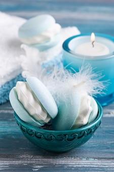 Kompozycja spa z makaronikiem z bomby do kąpieli i suchymi kwiatami na rustykalnym tle w stylu monochromatycznym. świece i sól. zabiegi kosmetyczne i relaksacyjne