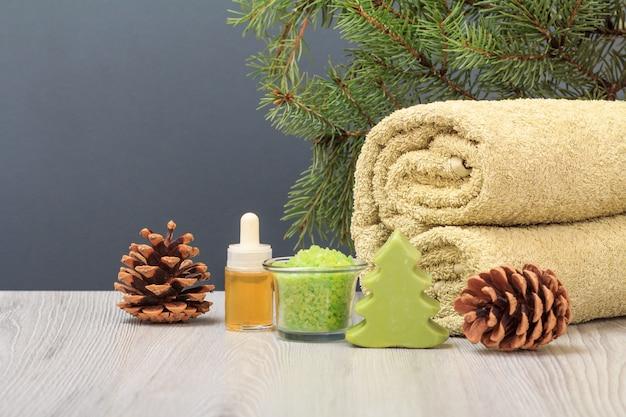 Kompozycja spa z miękkim ręcznikiem frotte, butelką z aromatycznym olejkiem, pudełkiem prezentowym, miską z solą morską, szyszkami i gałęzią jodły na szarym tle