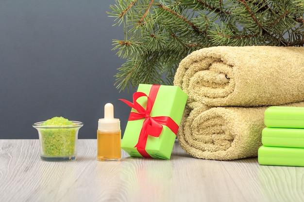Kompozycja spa z miękkim ręcznikiem frotte, pudełkiem prezentowym, butelką aromatycznego olejku, miską z solą morską i mydłem na szarym tle.