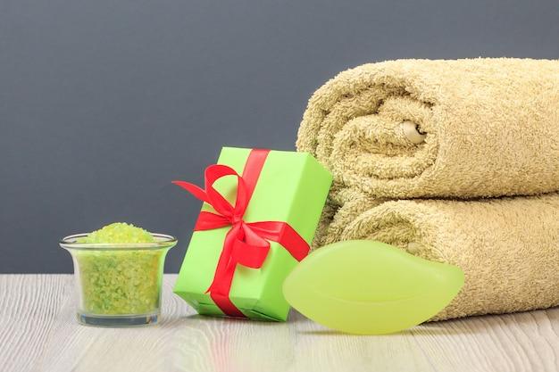Kompozycja spa z miękkim ręcznikiem frotte, pudełkiem prezentowym, miską z solą morską i mydłem na szarym tle.