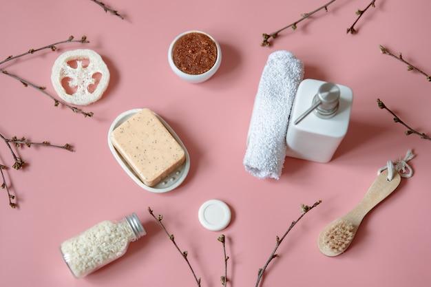 Kompozycja spa z mydłem, szczotką, luffą, solą morską i ręcznikiem wśród wiosennych gałęzi drzew.