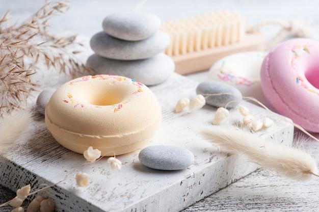 Kompozycja spa z pączkami bomby do kąpieli i suchymi kwiatami na rustykalnym tle w stylu monochromatycznym. świece i sól. zabiegi kosmetyczne i relaksacyjne