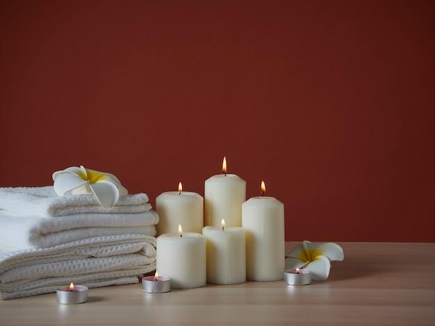 Kompozycja spa z palącymi aromatycznymi świecami i kwiatami plumeria na drewnianym stole