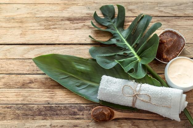Kompozycja spa z ręcznikami i liśćmi tropikalnymi