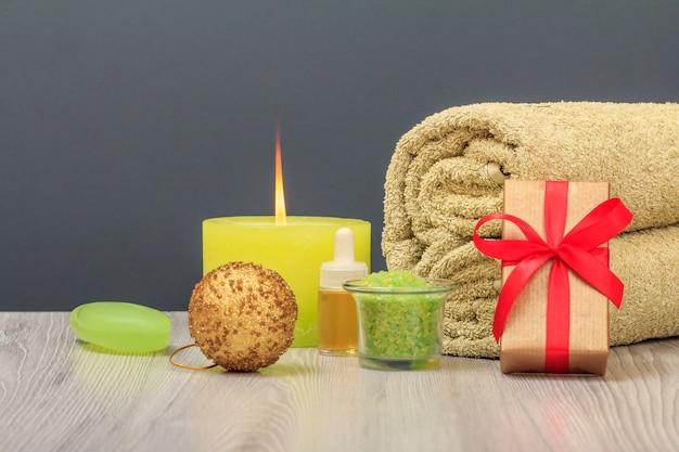 Kompozycja spa z ręcznikiem, pudełkiem prezentowym, olejkiem, solą morską i mydłem.