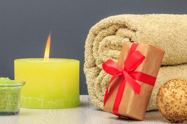 Kompozycja spa z ręcznikiem, pudełkiem prezentowym, solą morską i świecą.