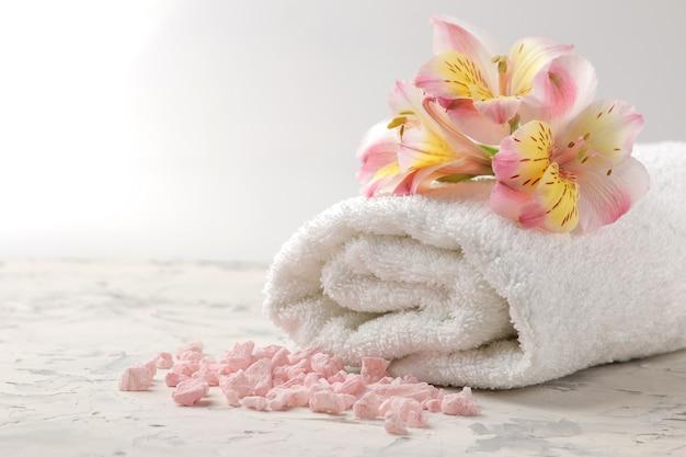 Kompozycja spa z ręcznikiem, solą morską i kwiatami. koncepcja spa. na jasnym tle.