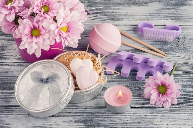 Kompozycja spa z różowymi bombami do kąpieli, kwiatami stokrotki, zapaloną świecą