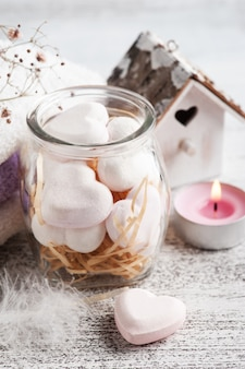 Kompozycja spa z sercami bomb do kąpieli i suchymi kwiatami na rustykalnej ścianie w stylu monochromatycznym. świece i sól. zabiegi kosmetyczne i relaksacyjne